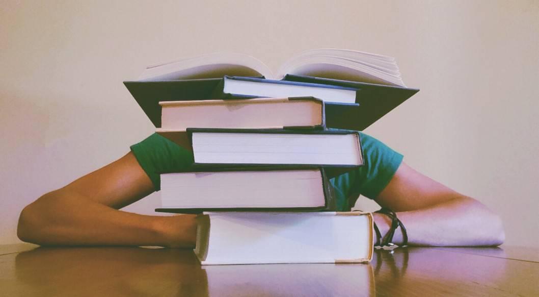 Bücher mit einem schlafenden Studenten dahinter
