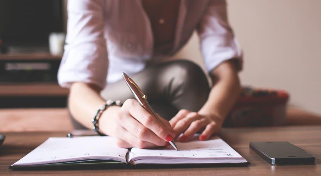Frau mit Notizbuch und Smartphone