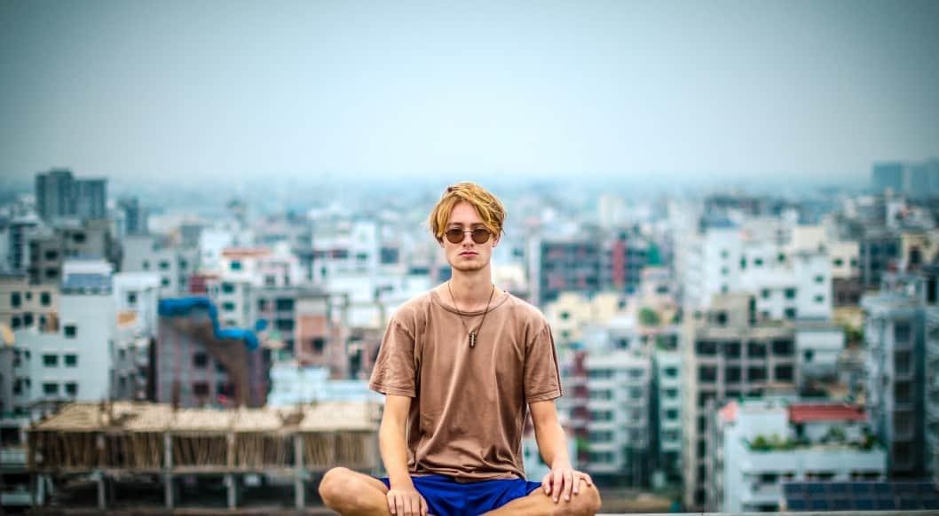 Junger Mann meditiert auf Dach